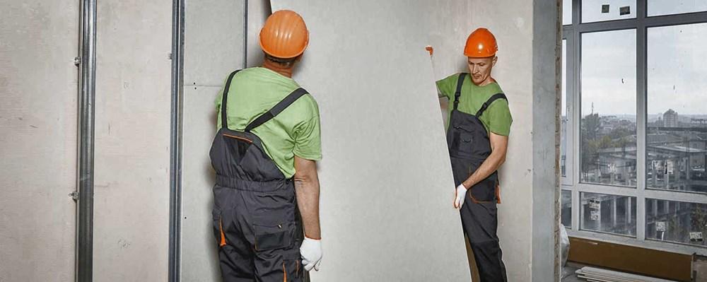 montadores segurando placa drywall gypsum